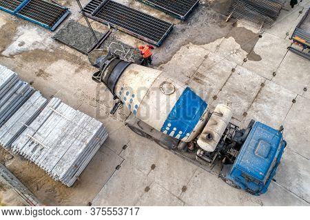 A Concrete Mixer Truck Transports Concrete Through A Construction Site. Transposing Liquid Concrete