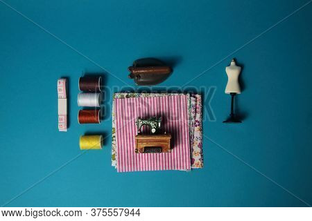 Sewing Machine, Tailor's Dummy, Skeins Of Thread For Needlework, Iron, Tape-measure, Fabric On Blue