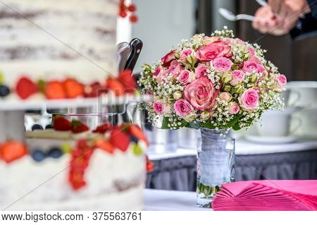 Selctive Focus Beautiful Wedding Flower Bouquet Behind Delicious Wedding Cake In Many Tiers With Fre