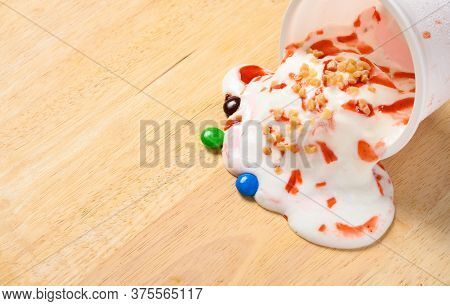 Cup Of Fresh Strawberry And Vanilla Flavor Ice Cream Sundae Melting With Chocolate Buttons Next To I