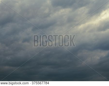 Dark Gray Heavy Clouds In The Sky Before A Thunderstorm. Dramatic Spectacular Backdrop Or Wallpaper.