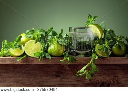 Carbonated Drink Or Cocktail With Limes And Mint On A Old Wooden Table. Green Background.