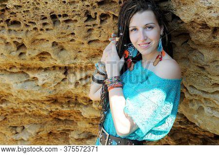 Indie, hippie style woman with dreadlocks portrait near rocks, outdoor