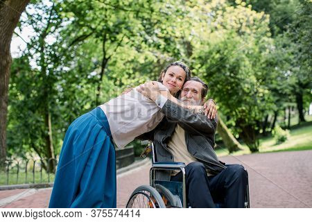 Disabled People, Palliative Care. Lifestyle Summer Portrait Of Senior Bearded Man In Wheelchair Hugg
