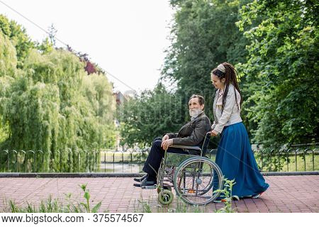 Side View Of Young Modern Hipster Woman With Long Dreadlocks, Assisting Her Disabled Grandfather On