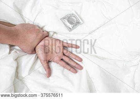 The Hands Of The Man And The Woman Are Touching On The Bed, With The Condom Placed Nearby That Is Re