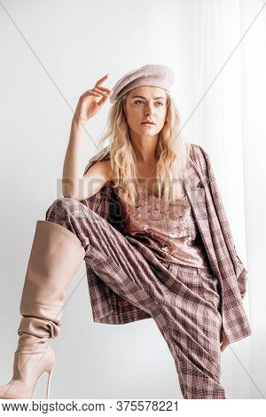 Beautiful Blonde Fashion Woman In Brow Checked Dress. Trendy Young Woman In Shabby Chic White Interi