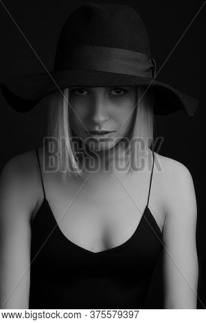 Black And White Portrait Blondes On Black Background In A Hat And Tank Top With Thin Straps