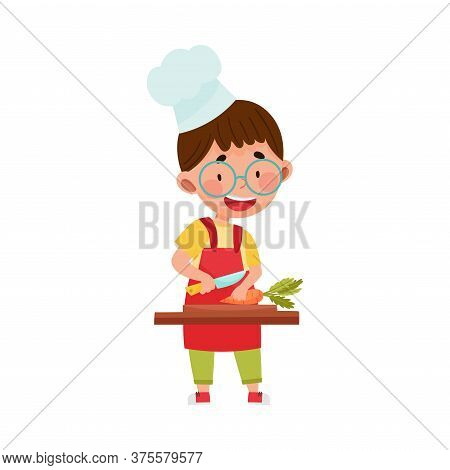 Smiling Boy Character In Hat And Apron Standing At Kitchen Table And Chopping Carrot Vector Illustra