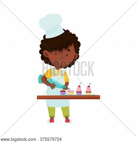 Little African American Girl Character In Hat And Apron Standing At Kitchen Table And Decorating Cup