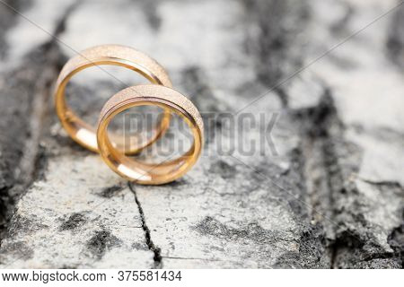 Beautiful wedding rings on wooden surface background. Declaration of love, spring. Wedding card, Valentine's Day greeting. Wedding rings. Wedding day details