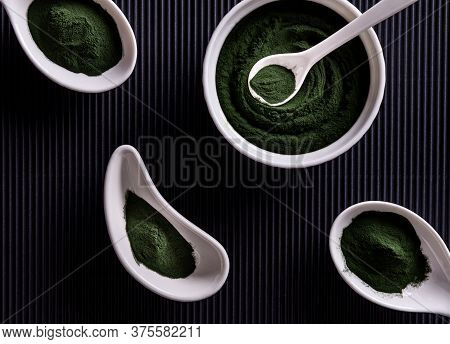 Natural Green Chlorella Or Spirulina Powder In Four Differently Shaped White Porcelain Bowls. Health