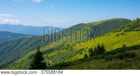 Summer Mountain Landscape. Green Hills Rolling In To The Distance. Fluffy Clouds On The Blue Sky Abo