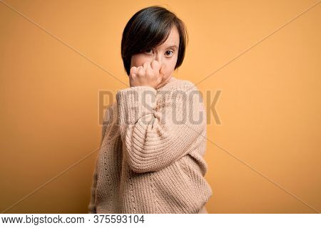 Young down syndrome woman wearing casual sweater over yellow background smelling something stinky and disgusting, intolerable smell, holding breath with fingers on nose. Bad smell