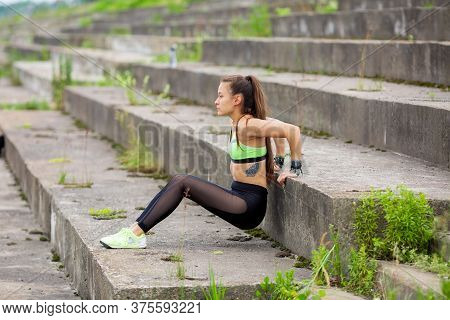 Athletic Young Girl Push-ups From The Floor On Stairs In City, Photography For A Healthy Lifestyle W