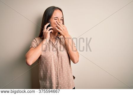 Young beautiful woman having conversation talking on the smartphone over white background smelling something stinky and disgusting, intolerable smell, holding breath with fingers on nose. Bad smell
