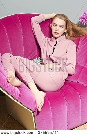 Beautiful girl having a rest  on pink armchair in her cozy home. Home interior, furniture. Lifestyle.
