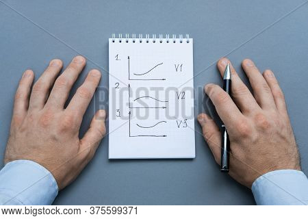 A Notebook With Charts Of Options Of Development Of Events And Pen Ready To Be Used. Male About To W