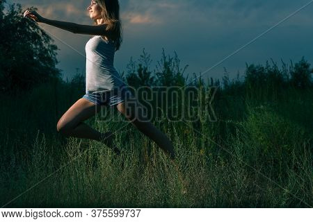 The Sporty Girl Runs In The High Grass At Night. She Dances Or Jumps Full Of Young Fever And Energy.