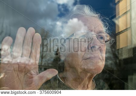 An Elderly Old Woman Looks Sadly Out The Window. Coronavirus Concept Stay In The House. Care For Lon