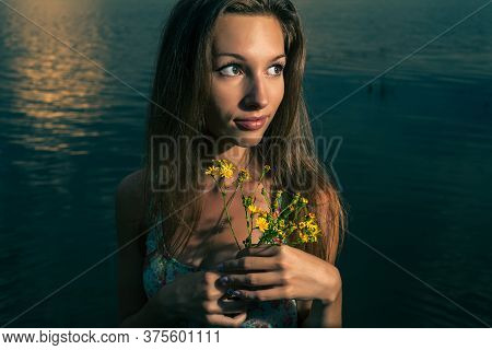 Young Girl Posing With Bouquet Of Wildflowers On The Sunset Panorama Of River