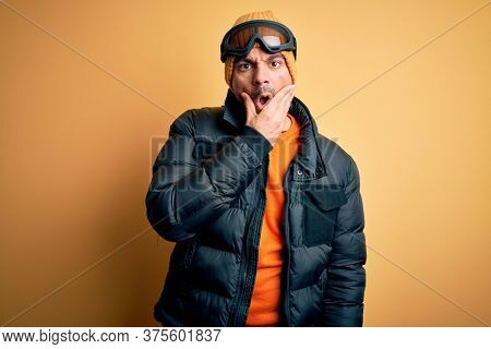 Young handsome skier man skiing wearing snow sportswear using ski goggles Looking fascinated with disbelief, surprise and amazed expression with hands on chin