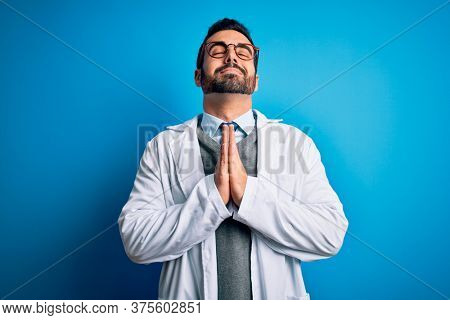 Young handsome doctor man with beard wearing coat and glasses over blue background begging and praying with hands together with hope expression on face very emotional and worried. Begging.