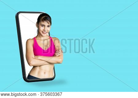 Young Asian Fitness Trainer Smile Thru Smartphone Screen In Concept Tech Service Of Online Health, F