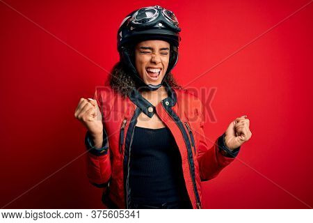Young african american motorcyclist girl wearing moto helmet and glasses over red background very happy and excited doing winner gesture with arms raised, smiling and screaming for success.