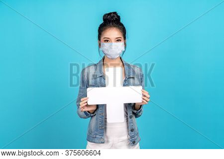 Happy Asian Woman Wear Surgical Mask Showing Plus, White Cross Or Add Paper Card Sign On Blue Backgr