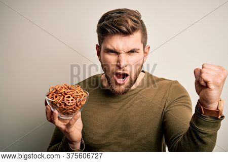 Young blond German man with beard and blue eyes holding bowl with baked pretzel annoyed and frustrated shouting with anger, crazy and yelling with raised hand, anger concept