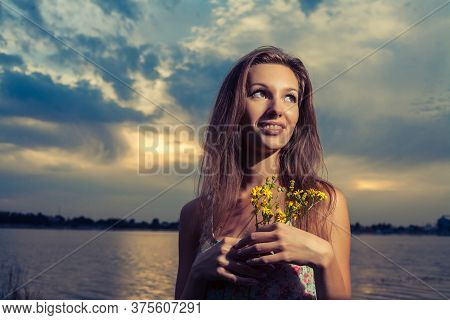 Young Woman Posing On The Sunset Panorama Of River