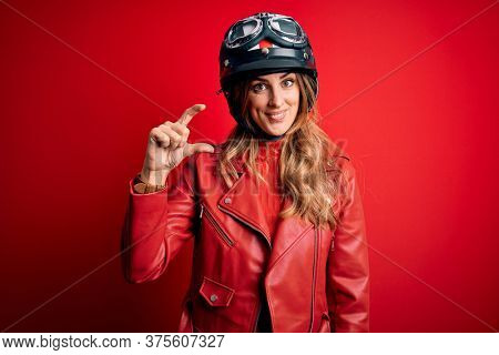 Young beautiful brunette motrocyclist woman wearing moto helmet over red background smiling and confident gesturing with hand doing small size sign with fingers looking and the camera. Measure concept