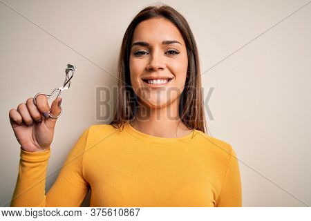 Young beautiful brunette woman holding eyelash curler over isolated white background with a happy face standing and smiling with a confident smile showing teeth