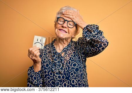 Senior beautiful grey-haired woman holding reminder paper with sad emotion face stressed with hand on head, shocked with shame and surprise face, angry and frustrated. Fear and upset for mistake.
