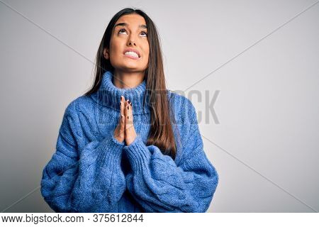 Young beautiful brunette woman wearing casual turtleneck sweater over white background begging and praying with hands together with hope expression on face very emotional and worried. Begging.