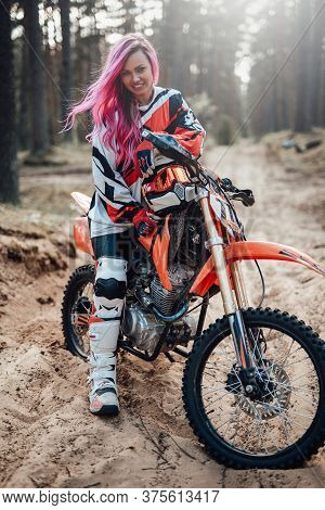 Beautiful Racer Girl With Pink Hair In Motocross Kit Sitting On Her Motorcycle In Off Road Adventure