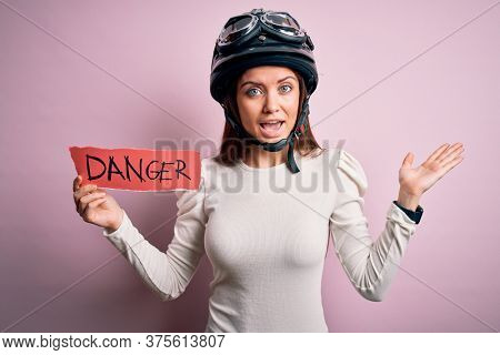 Beautiful motorcyclist woman with blue eyes wearing moto helmet holding danger message very happy and excited, winner expression celebrating victory screaming with big smile and raised hands