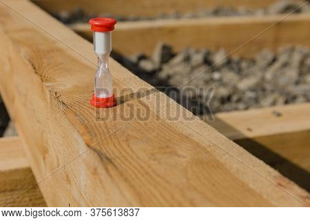 Wooden Beam, Hourglass On The Beam, Preparation Of The Foundation For The Construction Of A New Hous