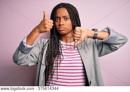 Young african american business woman standing over pink isolated background Doing thumbs up and down, disagreement and agreement expression. Crazy conflict