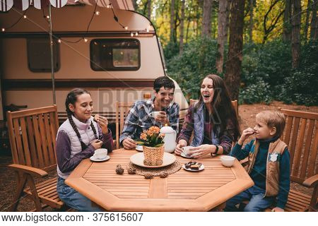 Happy Family On A Camping Trip Relaxing In The Autumn Forest. Camper Trailer. Fall Season Outdoors T
