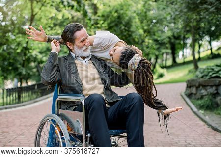 Portrait Of Handsome Bearded Elderly Man Sitting In Wheelchair In A City Park, Happy To See His Crea