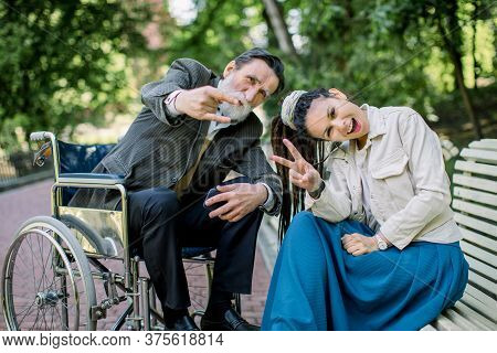 Portrait Of Young Hipster Modern Girl With Dreadlocks, Sitting On Bench, With The Senior Handicapped
