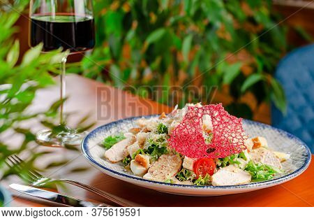 Caesar Salad With Grilled Chicken Breast, Romaine Lettuce, Eggs And Croutons Served With Red Wine. C