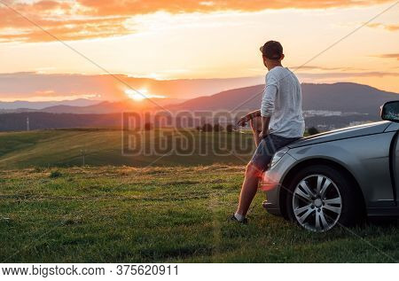 Young Man Having The Long Auto Trip Break. He Stoped New Car, Standing Near His Vehicle And Enjoying
