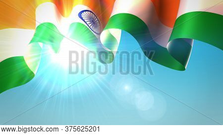 The Sun Shines Through The Waving Flag Of India. Waving Indian Flag On Blue Sky For Banner Design. F
