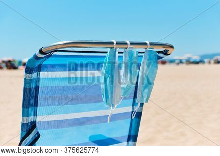 closeup of some surgical masks hanging on a blue deck chair on the beach, with the sea in the background
