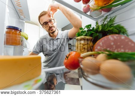 Man Looking For Something To Eat At Night While Standing In Front Of Opened Fridge. Unhealthy Eating