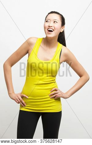Happy young woman in yellow tank top with hands on hips looking away against white background