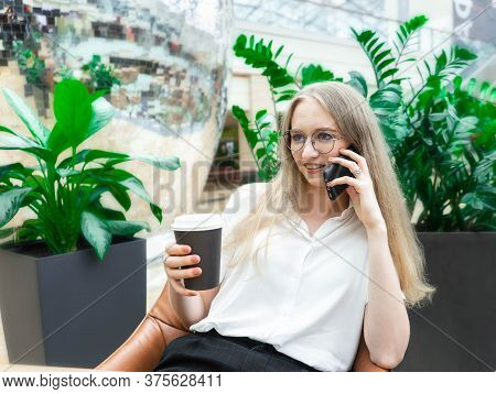 A Beautiful Cheerful Young Caucasian Blond Business Woman Sitting On The Table, Talking At Phone, Sm